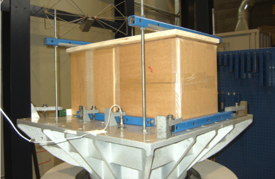 The vibration test is performed with boxes, including products, mounted on top of a vibrator by means of a 20 mm laminated wooden plate and yokes. The boxes are rotated and tested in all three axis.